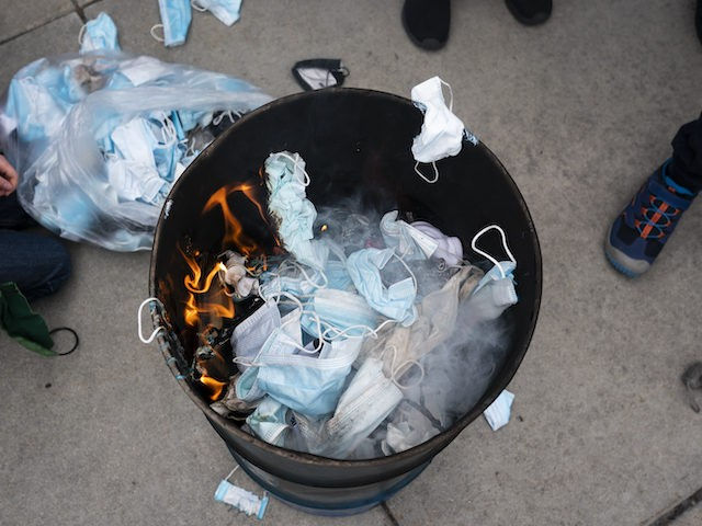 BOISE, ID - MARCH 06: Attendees toss surgical masks into a fire during a mask burning event at the Idaho Statehouse on March 6, 2021 in Boise, Idaho. Citizens and politicians, including the Lieutenant Governor Janice McGeachin, gathered in at least 20 cities across the state to protest COVID-19 restrictions. …