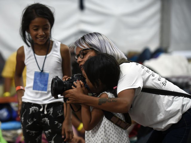 A photographer shows a migrant girl how to use her camera, at a stadium-turned-shelter in Mexico City, where Central American migrants - mostly Hondurans- who are taking part in a caravan towards the US, rest during a stop in their journey, on November 6, 2018. - A caravan of Central …