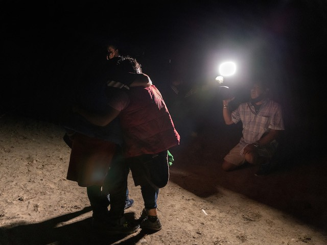 ROMA, TEXAS - APRIL 11: A TV crew films as Guatemalan immigrants embrace after they were smuggled across the Rio Grande from Mexico on April 11, 2021 in Roma, Texas. A surge of immigrants crossing into the United States, including record numbers of children, has challenged U.S. immigration agencies along the southern border. (Photo by John Moore/Getty Images)