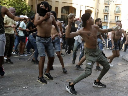 Anti-government protesters throw stones toward riot police during a protest marking the first anniversary of the massive blast at Beirut's port, near Parliament Square, In Beirut, Lebanon, Wednesday, Aug. 4, 2021. The grim anniversary comes amid an unprecedented economic and financial meltdown and a political stalemate that has kept the …