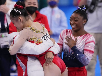 Aug 3, 2021; Tokyo, Japan; Xijing Tang (CHN), left, lifts up Chenchen Guan (CHN) after Guan finishes her balance beam routine as Simone Biles (USA) looks on during the Tokyo 2020 Olympic Summer Games at Ariake Gymnastics Centre. Mandatory Credit: Danielle Parhizkaran-USA TODAY Sports