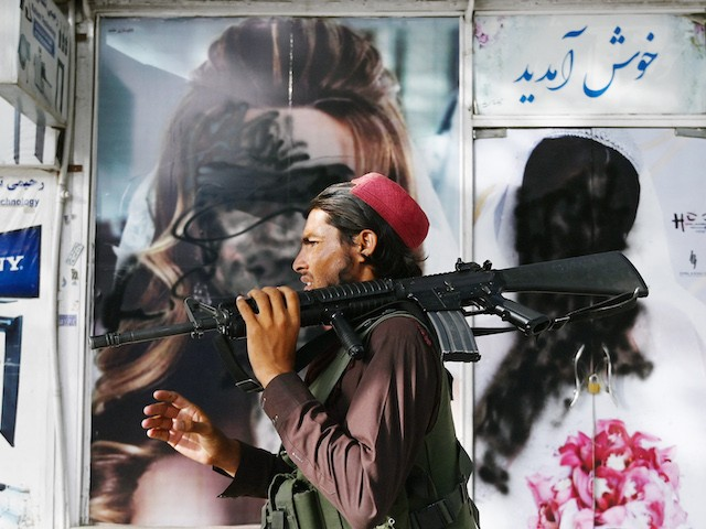 A Taliban fighter walks past a beauty salon with images of women defaced using spray paint in Shar-e-Naw in Kabul on August 18, 2021. (Photo by Wakil KOHSAR / AFP) (Photo by WAKIL KOHSAR/AFP via Getty Images)