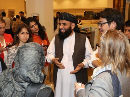 Suhail Shaheen (C), spokesman for the Taliban in Qatar, speaks to people as he attends the Intra Afghan Dialogue talks in the Qatari capital Doha on July 8, 2019. - Dozens of powerful Afghans met with a Taliban delegation on July 8, amid separate talks between the US and the …