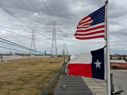 HOUSTON, TEXAS - FEBRUARY 21: The U.S. and Texas flags fly in front of high voltage transmission towers on February 21, 2021 in Houston, Texas. Millions of Texans lost power when winter storm Uri hit the state and knocked out coal, natural gas and nuclear plants that were unprepared for …