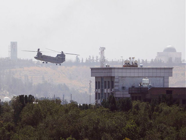 A U.S. Chinook helicopter flies near the U.S. Embassy in Kabul, Afghanistan, Sunday, Aug. 15, 2021. Helicopters are landing at the U.S. Embassy in Kabul as diplomatic vehicles leave the compound amid the Taliban advanced on the Afghan capital. (AP Photo/Rahmat Gul)