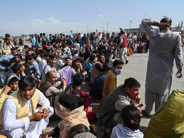 TOPSHOT - Afghan passengers sit as they wait to leave the Kabul airport in Kabul on August 16, 2021, after a stunningly swift end to Afghanistan's 20-year war, as thousands of people mobbed the city's airport trying to flee the group's feared hardline brand of Islamist rule. (Photo by Wakil …