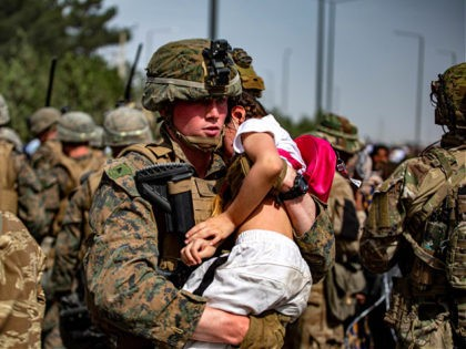 In this Aug. 20, 2021, photo provided by the U.S. Marine Corps, a Marine assigned to the 24th Marine Expeditionary Unit carries a girl at a gate to Hamid Karzai International Airport in Kabul, Afghanistan. (1st Lt. Mark Andries/U.S. Marine Corps via AP)