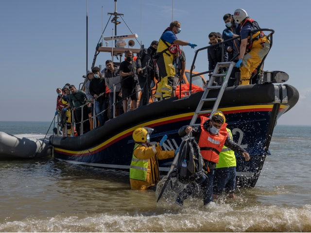 """DUNGENESS, ENGLAND - AUGUST 04: A group of around 40 migrants arrive via the RNLI (Royal National Lifeboat Institution) on Dungeness beach on August 04, 2021 in Dungeness, England. UK Home Secretary Priti Patel recently said that the government would seek to criminalise irregular migration, accusing people smugglers of """"exploiting …"""