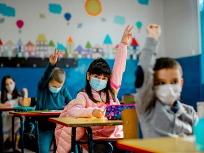 Elementary schoolchildren wearing a protective face masks in the classroom. Education during epidemic. - stock photo