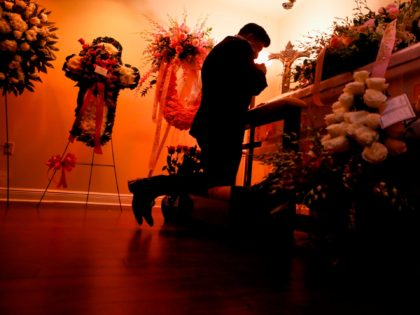 """Eduardo Antonio, Cuban singer, and friend of the late Cuban American singer and film actress Rosita Furnes kneels in front of her coffin during the funeral at Auxiliadora Funeria Nacional in Miami, Florida on June 12, 2020. - Family members and fans of Rosita Fornés, the """"Cuban Marilyn Monroe"""" who …"""