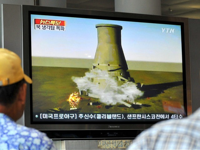 South Koreans watch a TV news programme at a railway station in Seoul, on June 27, 2008 that shows a mock video of the planned blow-up of a cooling tower at North Korea's Yongbyon nuclear complex. Secretive North Korea was preparing a global TV spectacular to dramatise its commitment to …