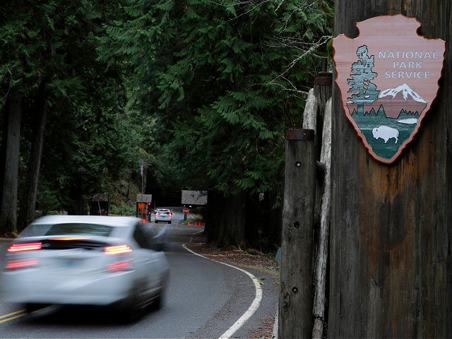 FILE - In this Jan. 28, 2019, file photo, a car drives past the Nisqually entrance to Mount Rainier National Park in Washington state. After closing amid the coronavirus pandemic, the National Park Service is testing public access at several parks across the nation, including two in Utah, with limited …