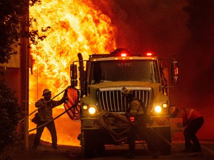 TOPSHOT - A firefighter saves an American flag as flames consume a home during the Dixie fire in Greenville, California on August 4, 2021. - The Dixie fire burned through dozens of homes and businesses in downtown Greenville and continues to forge towards other residential communities. Officials in northern California …