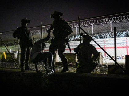 In this picture taken in the late hours on August 22, 2021 British and Canadian soldiers help an Afghan climb up on the wall of a canal as he with others wait near the foreign military-controlled part of the airport in Kabul, hoping to flee the country following the Taliban's …