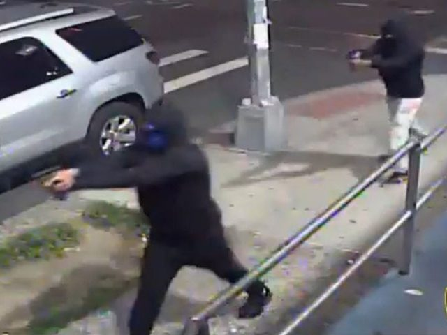Two masked and hooded men walked up to a crowd near a laundromat and barbershop in the New York City borough of Queens and opened fire, wounding 10 people, including three known gang members, before escaping on mopeds, police said Sunday morning.