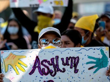 A migrant holds a sign during a protest against US and Mexican migration policies at the San Ysidro crossing port, in Tijuana, Baja California state, Mexico, on the border with the US, on October 21, 2020, amid the new coropnavirus pandemic. - With the implementation of the Migrant Protection Protocol …