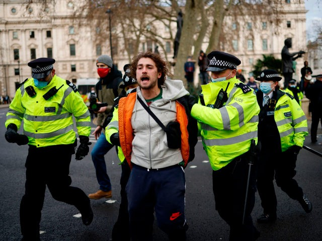 Police officers arrest a protestor during an anti-COVID-19 lockdown demonstration outside the Houses of Parliament in Westminster, central London on January 6, 2021. - Britain toughened its coronavirus restrictions on Tuesday, with England and Scotland going into lockdown and shutting schools, as surging cases have added to fears of a …