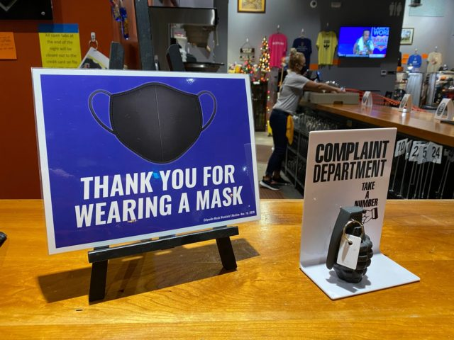 """Wearing a mask, a worker at Dodge City Brewing in Kansas cleans the bar behind a sign reminding customers they are required to wear a mask inside when not eating or drinking, next to a \""""complaint department\"""" sign with a mock grenade. Xxx Xxx Th Dodge City Coronavirus 666 Jpg …"""