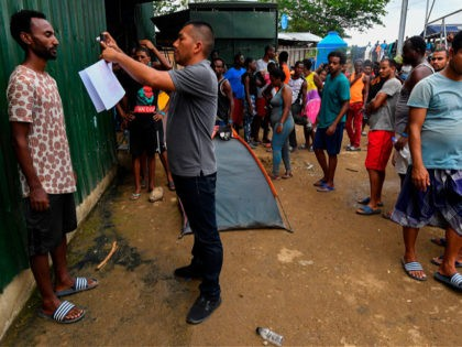 A member of Panama's National Borders Service takes a picture of a migrant at the Temporary Station of Humanitarian Assistance (ETAH) in La Penita village, Darien province, Panama on May 23, 2019. - Migrants mainly from Haiti, Cuba, Democratic Republic of Congo, India, Cameroon, Bangladesh and Angola cross the border …
