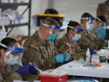 NORTH MIAMI, FLORIDA - MARCH 10: U.S. Army soldiers from the 2nd Armored Brigade Combat Team, 1st Infantry Division, prepare Pfizer COVID-19 vaccines to inoculate people at the Miami Dade College North Campus on March 10, 2021 in North Miami, Florida. The soldiers deployed to assist the Federal Emergency Management …