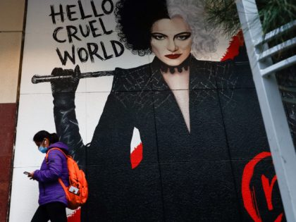 A masked pedestrian walks past a poster for the film Cruella in downtown Melbourne on August 6, 2021, amid a sixth lockdown for the city in efforts to bring the Delta outbreak to heel. (Photo by Con Chronis / AFP) (Photo by CON CHRONIS/AFP via Getty Images)