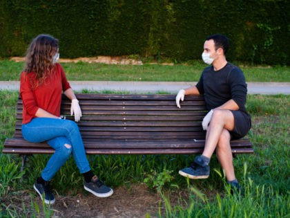 man and woman sitting on a bench in the park, keeping social distance wearing mask and gloves. Covid lifestyle - stock photo Covid 19 lifestyle coronavirus