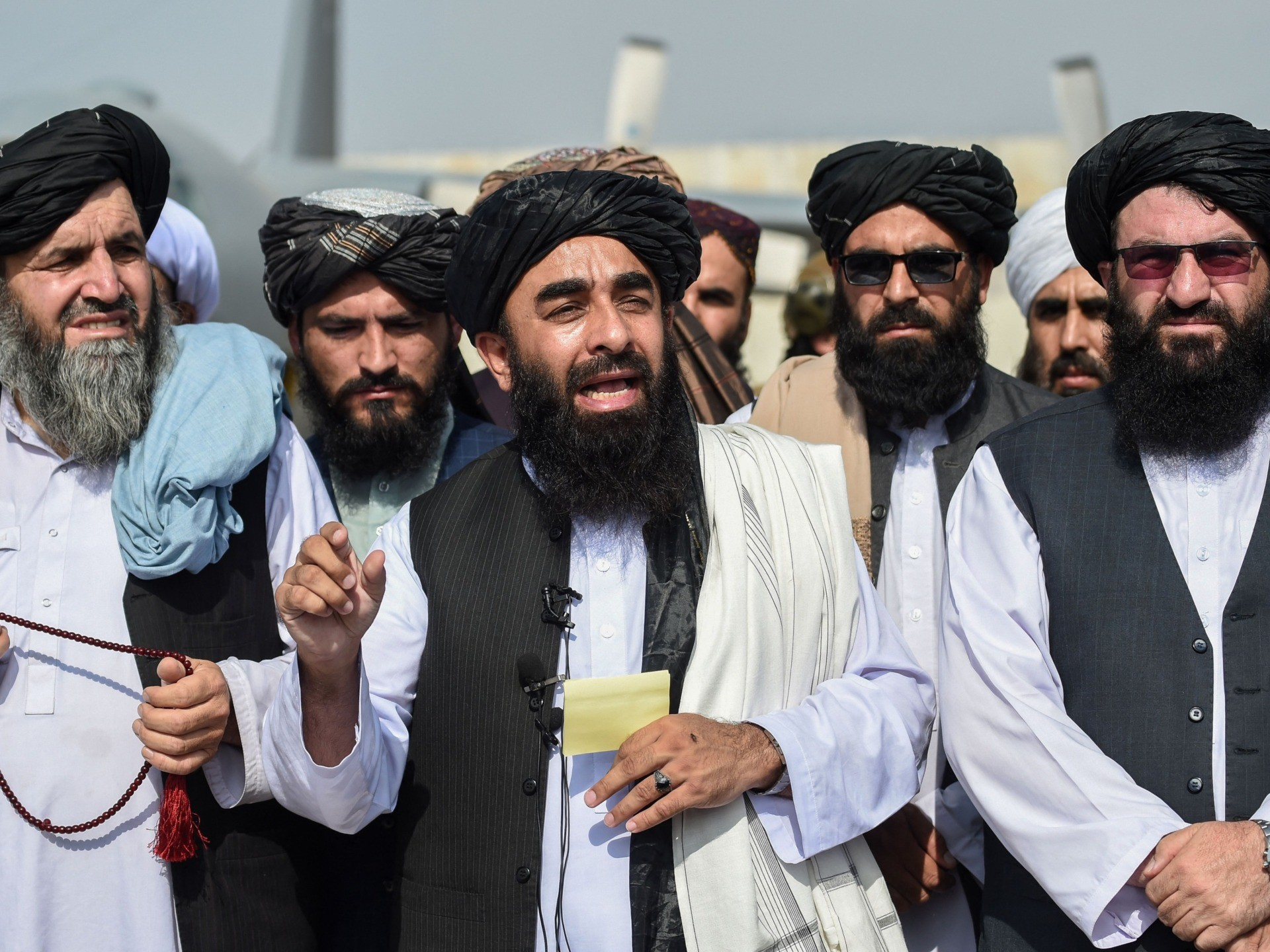 Taliban spokesman Zabihullah Mujahid (C) addresses a media conference at the airport in Kabul on August 31, 2021. - The Taliban joyously fired guns into the air and offered words of reconciliation on August 31, as they celebrated defeating the United States and returning to power after two decades of war that devastated Afghanistan. (Photo by WAKIL KOHSAR / AFP) (Photo by WAKIL KOHSAR/AFP via Getty Images)