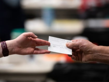 A patient receives a card showing when they received their first dose of the Pfizer Covid-19 vaccine at the Amazon Meeting Center in downtown Seattle, Washington on January 24, 2021. - Amazon is partnering with Virginia Mason for a one-day pop-up clinic on January 24. 2021 that aims to vaccinate …