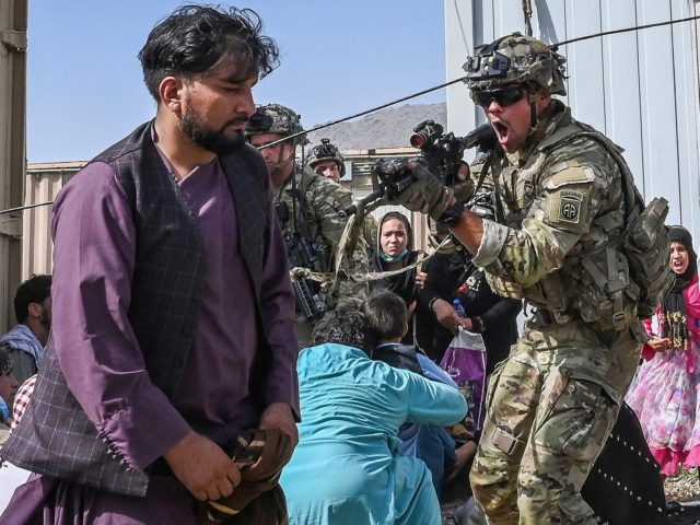 A US soldier (C) point his gun towards an Afghan passenger at the Kabul airport in Kabul on August 16, 2021, after a stunningly swift end to Afghanistan's 20-year war, as thousands of people mobbed the city's airport trying to flee the group's feared hardline brand of Islamist rule. (Photo …