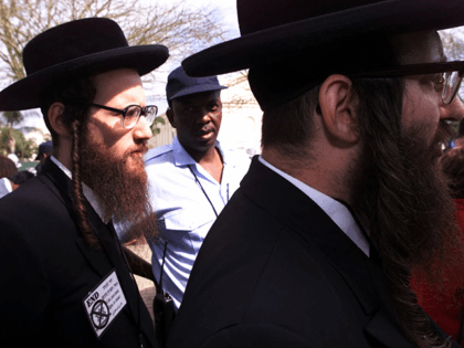 A policeman, center, watches as Rabbis Yisroel Dovid Weiss, right, and Dovid Da Feldman, left, join a demonstration at the UN Racism Conference in Durban, South Korea, Tuesday, Sept. 4, 2001, protesting the US and Israeli pullout from the conference. The countries pulled out Monday denouncing efforts to condemn Israel …