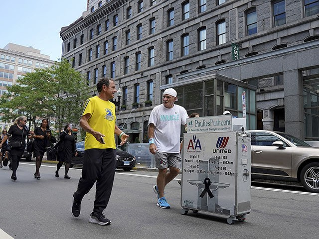 Paul Veneto, right, is joined by Boston Marathon Race Director Dave McGillivray, front left, as Veneto pushes a beverage cart along State Street, in Boston, Saturday, Aug. 21, 2021. Veneto, a former flight attendant who lost several colleagues when United Flight 175 was flown into the World Trade Center on …