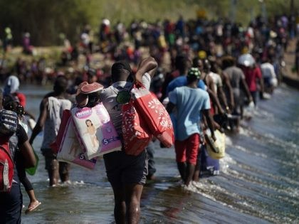 Haitian migrants use a dam to cross to and from the United States from Mexico, Friday, Sept. 17, 2021, in Del Rio, Texas. Thousands of Haitian migrants have assembled under and around a bridge in Del Rio presenting the Biden administration with a fresh and immediate challenge as it tries …