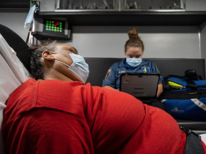 A patient experiencing a coronavirus emergency speaks with a member of Louisville Metro Emergency Medical Services in an ambulance outside of the patient's home on September 13, 2021 in Louisville, Kentucky. (Jon Cherry/Getty Images)