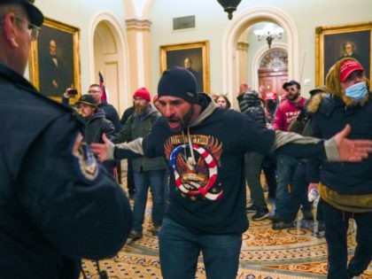 In this Jan. 6, 2021, file photo, Trump supporters, including Doug Jensen, center, confront U.S. Capitol Police in the hallway outside of the Senate chamber at the Capitol in Washington. Some followers of the QAnon conspiracy theory are now turning to online support groups and even therapy to help them …