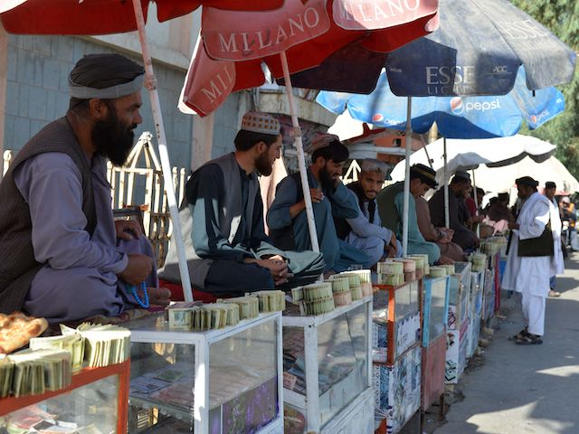 Money changers sit at the currency exchange market along a road in Kandahar on September 20, 2021. (Javed Tanveer/AFP via Getty Images)
