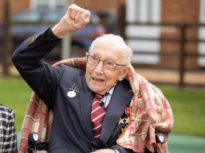 MARSTON MORETAINE, ENGLAND - In this handout image provided by Capture the Light Photography, Colonel Tom Moore and his daughter Hannah celebrate his 100th birthday, with an RAF flypast provided by a Spitfire and a Hurricane over his home on April 30, 2020 in Marston Moretaine, England. Colonel Moore, formerly …