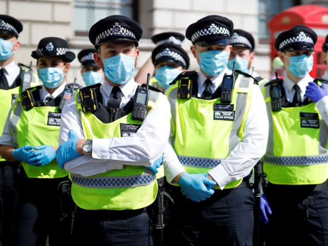 """Police officers wearing face masks and gloves due to the COVID-19 pandemic, stand on duty as activists from the climate protest group Extinction Rebellion demonstrate in Parliament Square in London on September 2, 2020, on the second day of their new season of """"mass rebellions"""". - Climate protest group Extinction …"""