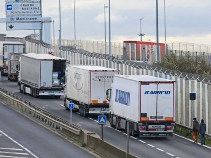 Migrants walk to climb into the back of lorries bound for Britain while traffic is stopped upon waiting to board shuttles at the entrance to the Channel Tunnel site on November 19, 2020, in Calais, northern France. - The French port of Calais continues to attract migrants from the Middle …