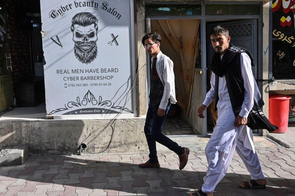 Men walk past a barbershop in Kabul on June 16, 2021. (Photo by ADEK BERRY / AFP) (Photo by ADEK BERRY/AFP via Getty Images)