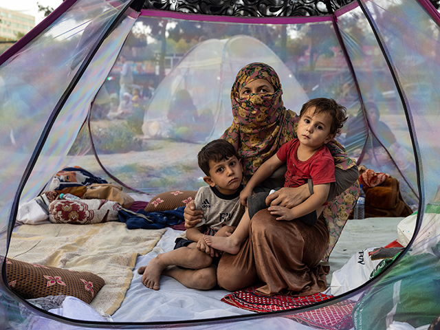 KABUL, AFGHANISTAN - AUGUST 12: Farzia, 28, who lost her husband in Baghlan one week ago to fighting by the Taliban sits with her children, Subhan, 5, and Ismael ,2, in a tent at a makeshift IDP camp in Share-e-Naw park to various mosques and schools on August 12, 2021 …