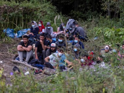 Migrants believed to be from Afghanistan sit on the ground in the small vilage of Usnarz Gorny near Bialystok, northeastern Poland, located close to the border with Belarus, on August 20, 2021. - The fate of 32 migrants stranded on the border between Belarus and Poland is rapidly becoming a …