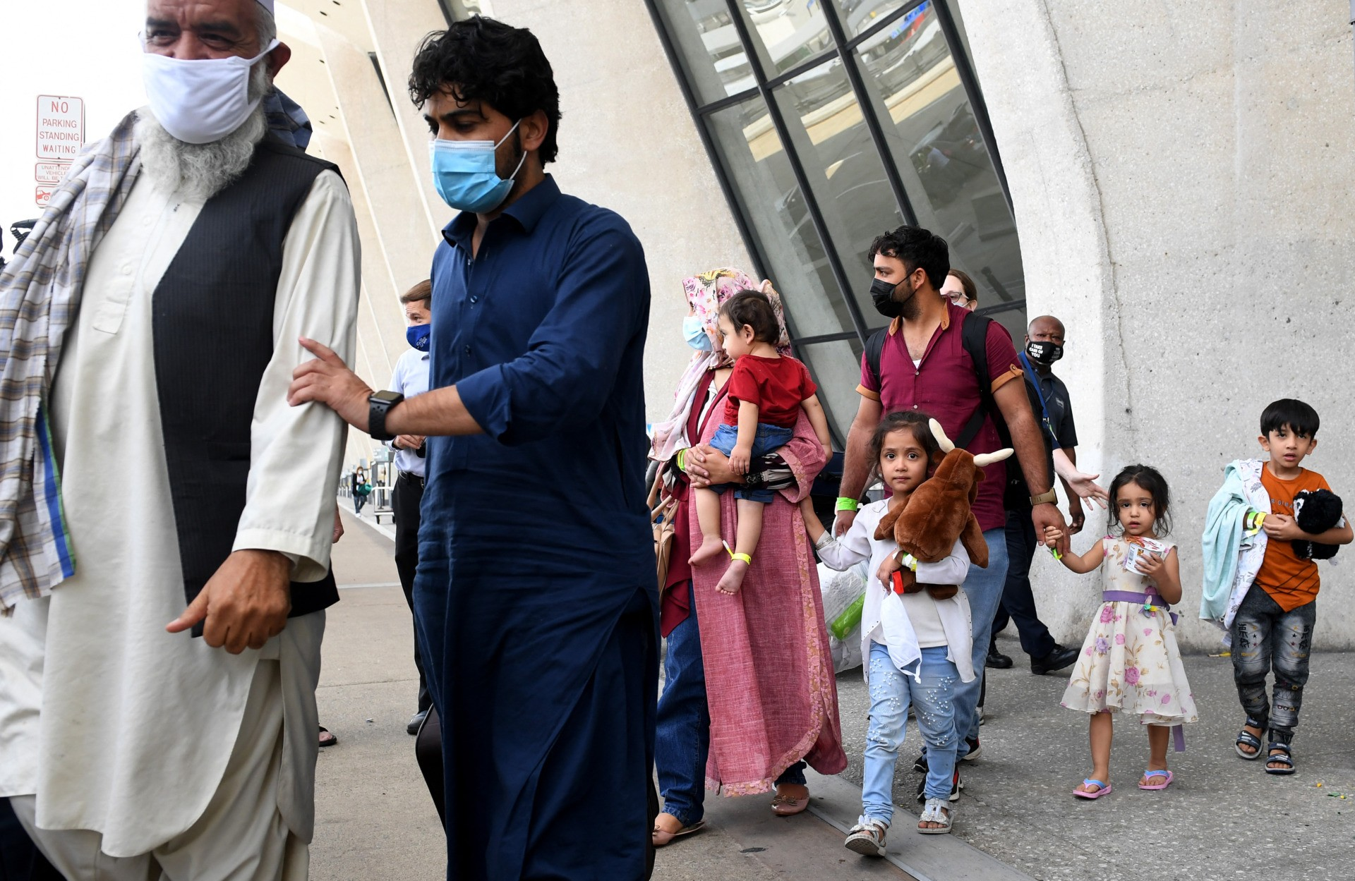 Afghan refugees arrive at Dulles International Airport on August 27, 2021 in Dulles, Virginia, after being evacuated from Kabul following the Taliban takeover of Afghanistan. - The Pentagon said on Friday the ongoing evacuation from Afghanistan faces more threats of attack a day after a suicide bomber and possible associated gunmen killed scores at a Kabul airport gate. (Photo by Olivier DOULIERY / AFP) (Photo by OLIVIER DOULIERY/AFP via Getty Images)