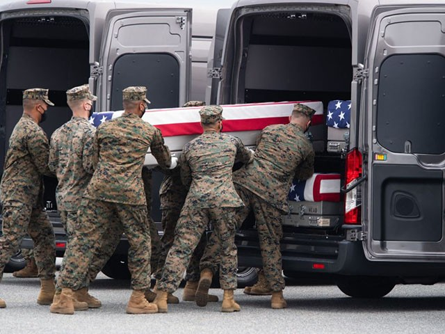 A flag-draped transfer case with the remains of a fallen service member are placed inside a transfer vehicle as US President Joe Biden attends the dignified transfer ceremony at Dover Air Force Base in Dover, Delaware, August, 29, 2021, one of the 13 members of the US military killed in Afghanistan last week. - President Joe Biden prepared Sunday at a US military base to receive the remains of the 13 American service members killed in an attack in Kabul, a solemn ritual that comes amid fierce criticism of his handling of the Afghanistan crisis. Biden and his wife, Jill, both wearing black and with black face masks, first met far from the cameras with relatives of the dead in a special family center at Dover Air Force Base in Delaware.The base, on the US East Coast about two hours from Washington, is synonymous with the painful return of service members who have fallen in combat. (Photo by SAUL LOEB / AFP) (Photo by SAUL LOEB/AFP via Getty Images)