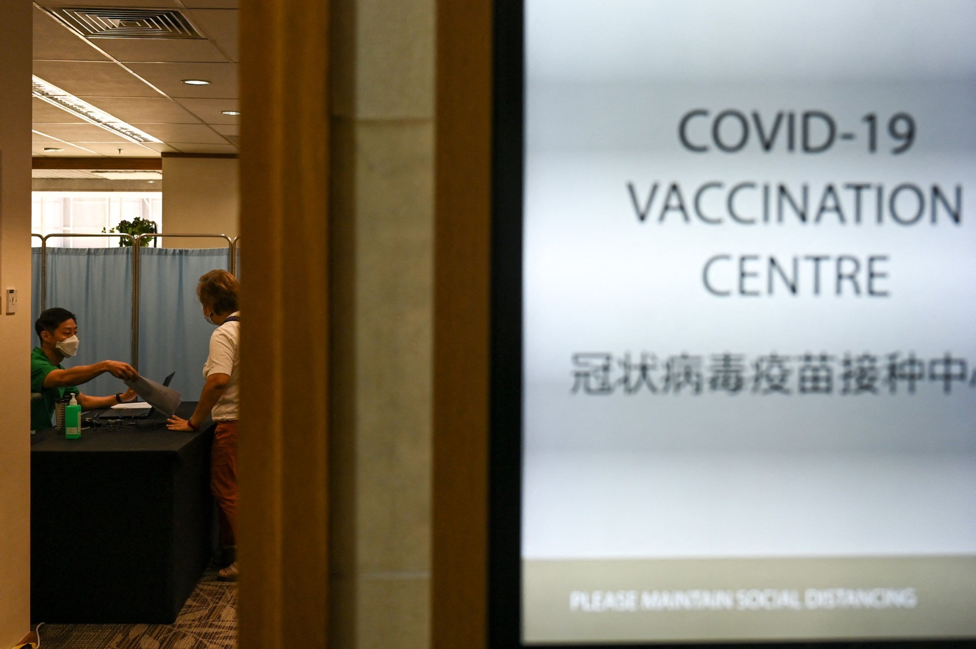 A medical staff attends to a woman before receiving a dose of the Sinopharm Covid-19 coronavirus vaccine at the Mount Elizabeth hospital vaccine centre in Singapore on September 7, 2021. (Photo by Roslan Rahman / AFP) (Photo by ROSLAN RAHMAN/AFP via Getty Images)