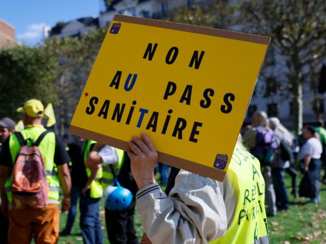 A demonstrator holds up a placard during a protest of Gilets Jaunes (yellow vest) and Citoyens en colere movements against the compulsory Covid-19 vaccination for certain workers, and the mandatory use of the health pass called for by the French government to access most public spaces, in Paris on September …