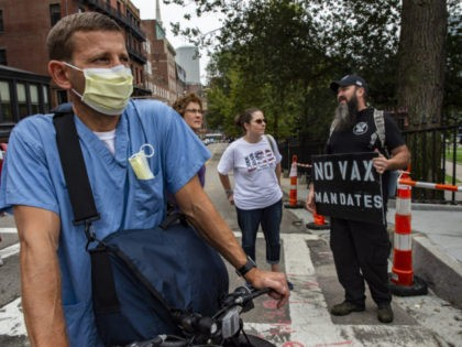 A nurse from Brigham and Women's Hospital watches as demonstrators gather outside the Massachusetts State House in Boston to protest Covid-19 vaccination and mask mandates. (Photo by JOSEPH PREZIOSO / AFP) (Photo by JOSEPH PREZIOSO/AFP via Getty Images)