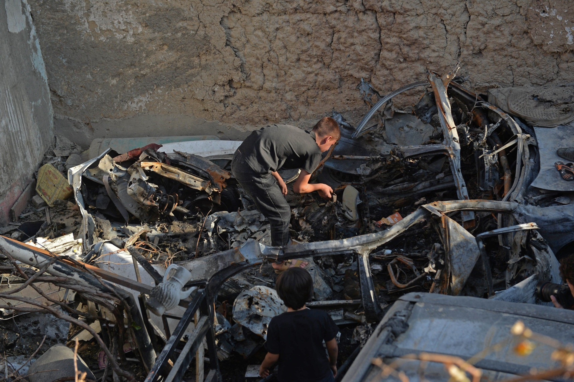 A relative of Ezmarai Ahmadi, inspects the debris of a vehicle that was damaged in a US drone strike in the Kwaja Burga neighbourhood of Kabul on September 18, 2021. - Ezmarai Ahmadi was wrongly identified as an Islamic State militant by US intelligence, who tracked his white Toyota for eight hours on August 29 before targeting the car, killing seven children and three adults. (Photo by Hoshang Hashimi / AFP) (Photo by HOSHANG HASHIMI/AFP via Getty Images)