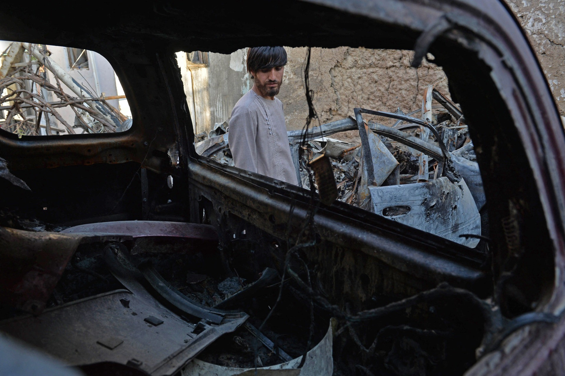 A relative of Ezmarai Ahmadi, is pictured through the wreckage of a vehicle that was damaged in a US drone strike in the Kwaja Burga neighbourhood of Kabul on September 18, 2021. - Ezmarai Ahmadi was wrongly identified as an Islamic State militant by US intelligence, who tracked his white Toyota for eight hours on August 29 before targeting the car, killing seven children and three adults. (Photo by Hoshang Hashimi / AFP) (Photo by HOSHANG HASHIMI/AFP via Getty Images)