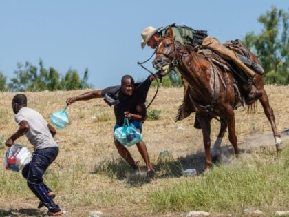TOPSHOT - A United States Border Patrol agent on horseback tries to stop a Haitian migrant from entering an encampment on the banks of the Rio Grande near the Acuna Del Rio International Bridge in Del Rio, Texas on September 19, 2021. - The United States said Saturday it would …