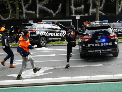 Demonstrators kick a police car during a protest against Covid-19 regulations in Melbourne on September 21, 2021. (Photo by STR / AFP) (Photo by STR/AFP via Getty Images)